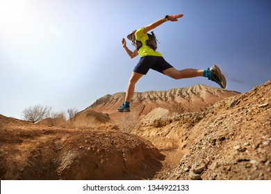 Runner athlete with beard jump over the canyon on the wild trail at red mountains in the desert