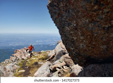 Runner athlete with beard in orange shirt running on the trail high in the mountains