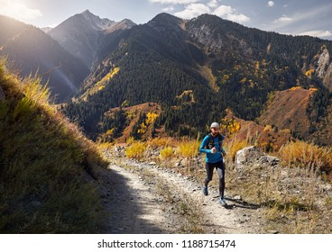 Runner athlete with beard running on the trail in the mountains