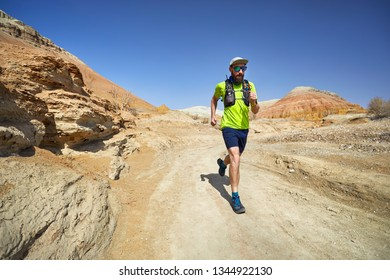 Runner athlete with beard running on the wild trail at clay mountains in the desert