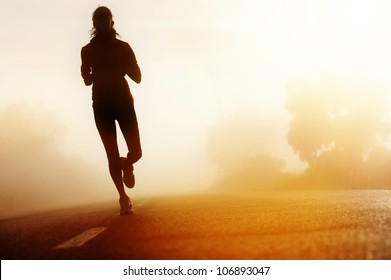 Runner athlete feet running on road. woman fitness silhouette sunrise jog workout wellness concept.