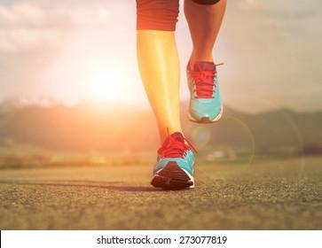 Runner athlete feet running on road under sunlight. - Shutterstock ID 273077819