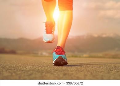 Runner athlete feet running on road under sunlight.