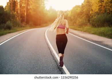 Runner athlete female running at forest road on sunset