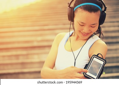 Runner athlete listening to music in headphones from smart phone mp3 player smart phone armband.woman fitness jogging workout wellness concept.