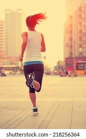 Runner athlete running on city street. woman fitness jogging workout wellness concept.