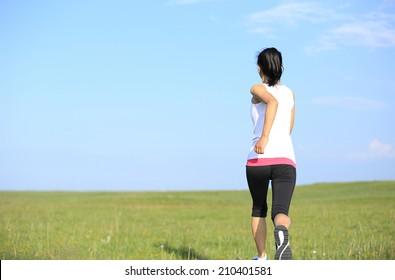 Runner athlete running on grass field. woman fitness jogging workout wellness concept.