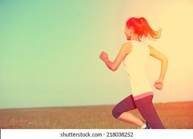 Runner athlete running on grass seaside. woman fitness sunrise/sunset jogging workout wellness concept.