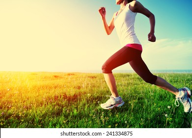 Runner athlete running on grass seaside. woman fitness sunset jogging workout wellness concept.