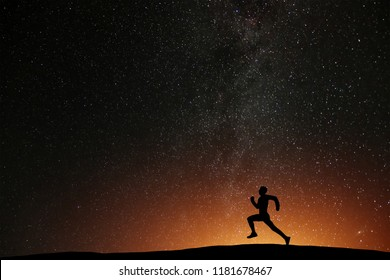 Runner athlete running on the hill with beautiful starry night background. Silhouette of man jogging workout in dark time, wellness concept.
