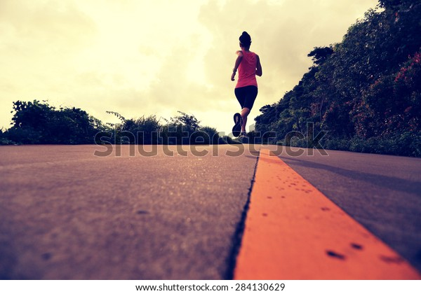 Runner athlete running at seaside road. woman fitness jogging workout wellness concept.