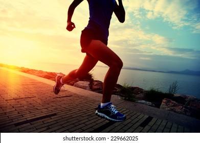 Runner athlete running at seaside. woman fitness sunrise jogging workout wellness concept.