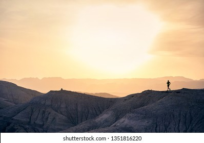 Runner athlete in silhouette running on the wild trail at mountains in the desert at sunset