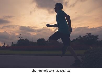 Runner athlete silhouette running in public park. man fitness sunrise jogging workout wellness concept.