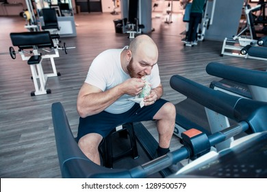 runner athlete while relaxing eating an ice cream on the driving machinery in the gym
