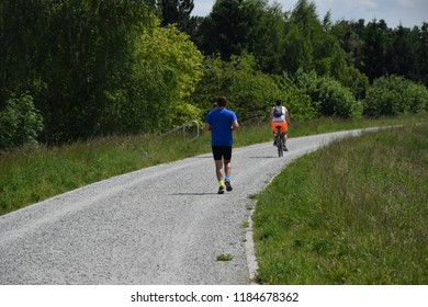 Runner and biker recreation time outdoors on the path between meadows and fields. Free time summer sports. Man running outdoors and having fun. People run and riding bicycle. Fir person, sportswear.