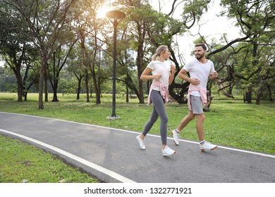 a runner couple is jogging in the park during summer season (healthy or sport concept)