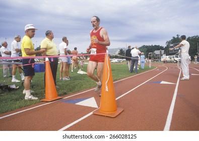 Runner crosses the finishing line at the Senior Olympics, St. Louis, MO