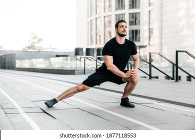 Runner doing side lunges. Portrait of sporty man doing stretching exercises before training. Male athlete preparing for jogging outdoors. Sport active lifestyle concept. Full length.