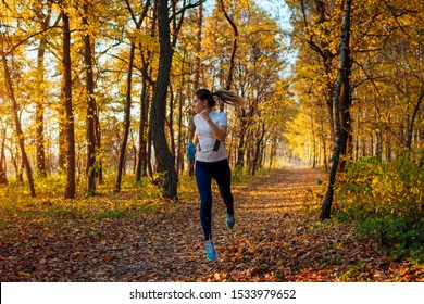 Runner exercising in autumn park. Woman running with water bottle at sunset. Active lifestyle. Healthcare