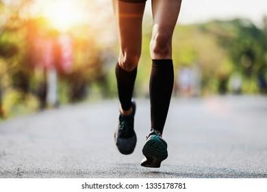 Runner feet running on asphalt road closeup