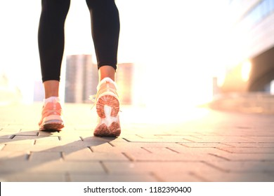 Runner feet running on road closeup on shoe, outdoor at sunset or sunrise in city