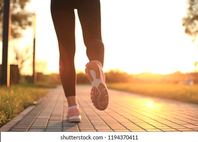 Runner feet running on road closeup on shoe, outdoor at sunset or sunrise.