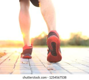 Runner feet running on road closeup on shoe, outdoor at sunset or sunrise