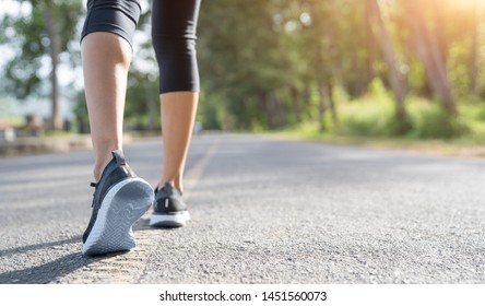 Runner feet running on road closeup on shoe. Woman fitness sunrise jog workout wellness concept. Young fitness woman runner athlete running at road