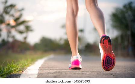Runner feet running on running road closeup on shoe. woman fitne