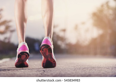 Runner feet running on running road closeup on shoe. woman fitnes