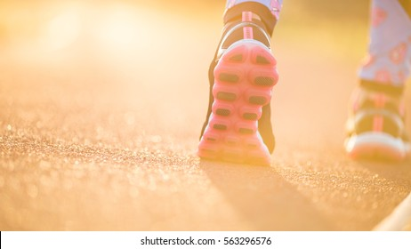 Runner feet running on road closeup on shoe. woman fitness sunrise jog workout welness concept