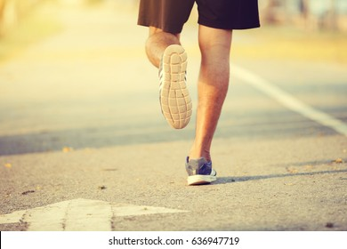 Runner feet running on road closeup on shoe,Men jogging on public road.