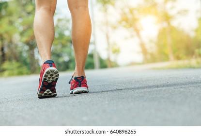 Runner feet running on road closeup on shoe