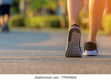 Runner feet running on the road in the outdoor workout park, closeup on shoe. Asian fitness woman running for healthy and relax.  Sport Concept