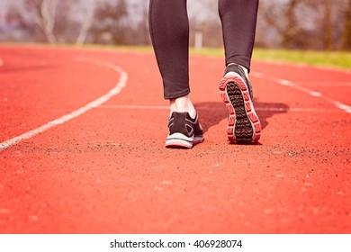 Runner feet running on stadium track closeup - woman running concept. Sunny Day