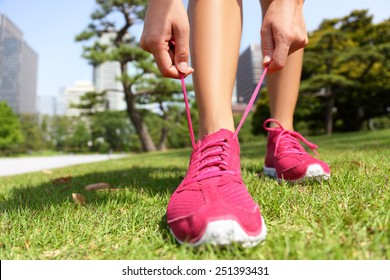 Runner getting ready for jogging tying running shoes laces - Woman preparing before run putting on trainers in japanese park near Ginza in Tokyo, Japan