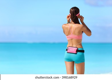 Runner girl getting ready for run on beach listening to music with earphones and smartphone holder fanny pack waist belt as sports gear wearing wearable tech activity tracker.
