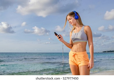 Runner girl looking smartphone at the beach