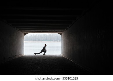 Runner in gray sportswear warming up in tunnel. Full length image