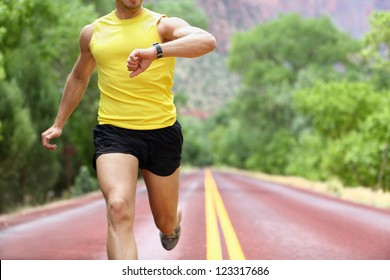 Runner with heart rate monitor sports smart watch. Man running looking at his pulse outside in nature on road with smartwatch.