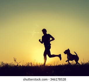 Runner and his dog sunset silhouettes