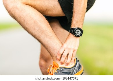 Runner holding sore leg, knee pain from running or exercising, jogging injury or cramp, cross country in summer nature