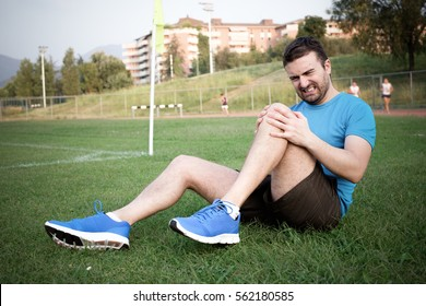 Runner with injured knee on the grass