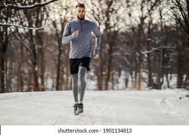 Runner jogging in nature at winter on snowy weather. Winter fitness, snowy weather, chilly