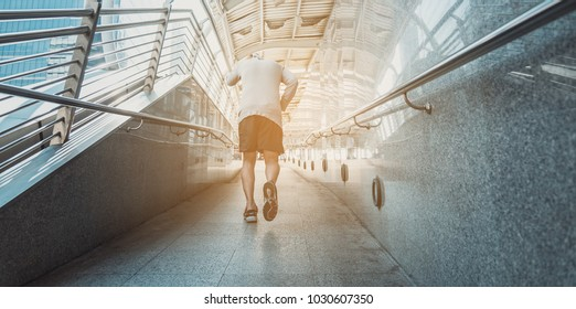 Runner jogging training and doing workout exercising power running outdoors in city. A handsome young man running in the city at morning. Sportsman fitness jog workout wellness concept