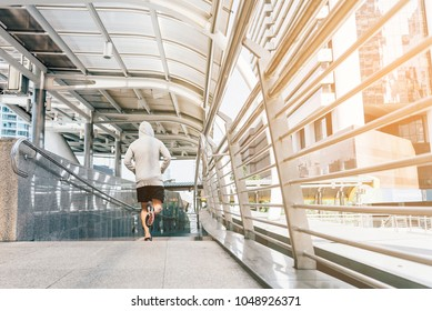 Runner jogging training and doing workout exercising power running outdoors in city.A handsome young man running in the city at morning.Sportsman fitness jog workout wellness concept