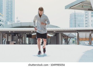 Runner jogging training and doing workout exercising power running outdoors in city.