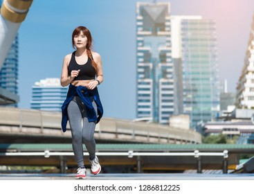 Runner jogging training and doing workout exercising power running outdoors in city. A young woman running in the city at morning. Sportswoman fitness jog workout wellness concept