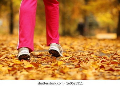Runner legs and running shoes. Sporty woman jogging walking outdoors in autumn park on forest path, fall colors golden leaves